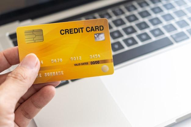 De creditcard van de mensenholding op laptop. online winkelen op internet met behulp van een laptop