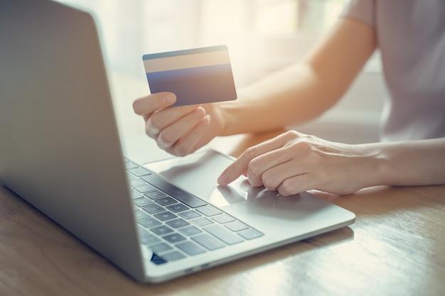 De creditcard van de vrouwenholding en het gebruiken van laptop