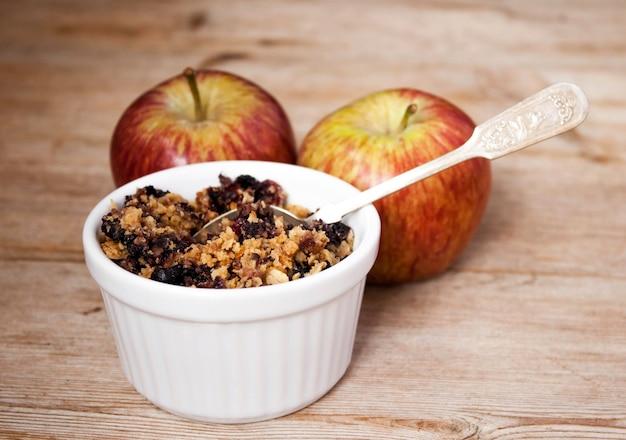 De crumble van de havermoutbosbes in ceramische kom en twee appels