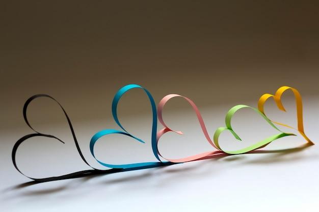 De dag abstracte achtergrond van valentine met gesneden document kleurrijke harten op wit.