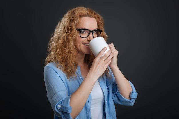 De dag beginnen. verbluffende actieve mooie vrouw die warme drank nipt uit een beker die ze vasthoudt terwijl ze geïsoleerd op een grijze achtergrond staat