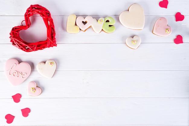 De dag houten hart van valentijnskaarten met hartkoekjes op witte houten achtergrond.