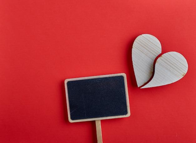 De dag houten hart van valentijnskaarten op rode achtergrond