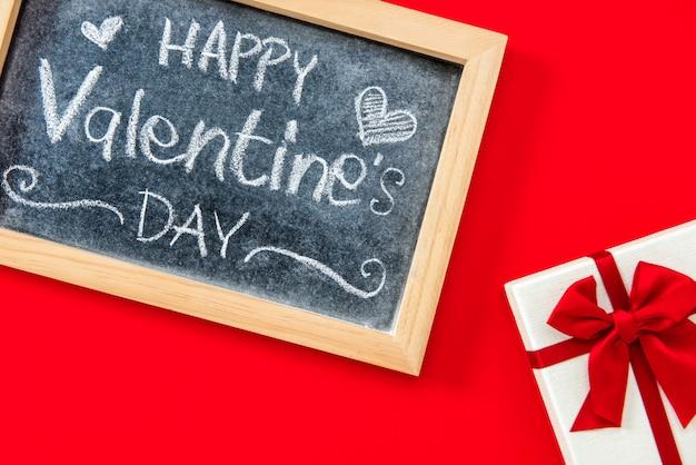 De dag met de hand geschreven tekst van happy valentine op bord met giftvakje