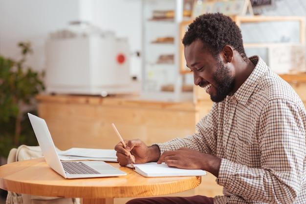 De dag plannen. vrolijke jonge man zit aan de tafel in het café en maakt aantekeningen in zijn dagelijkse planner, terwijl hij zijn agenda bepaalt terwijl hij breed lacht