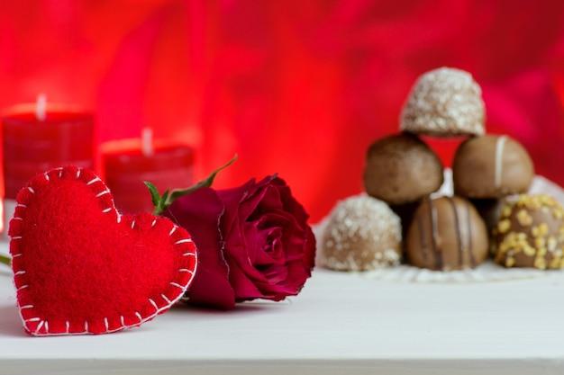 De dag rode achtergrond van valentine met rozen en chocolade.