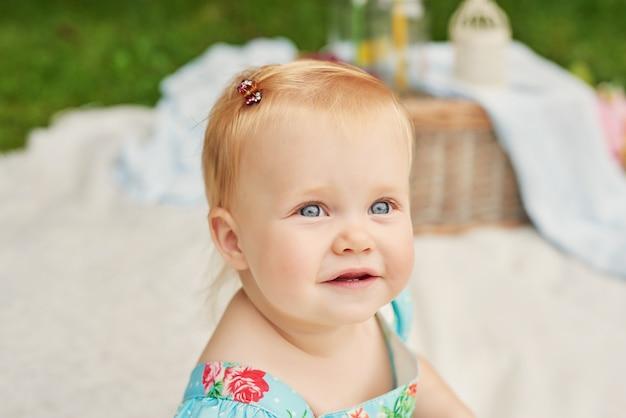 De dag van de kinderenbescherming, babymeisje in het park zit in een mand op een de zomerpicknick