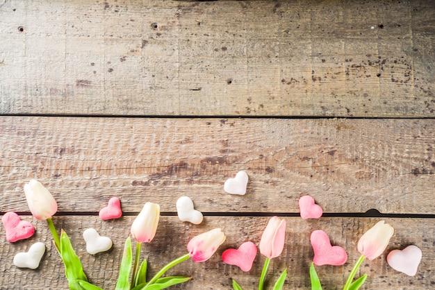De dagachtergrond van valentine met harten, bloemen