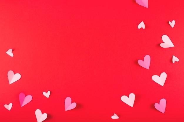 De dagachtergrond van valentine met harten op rood en exemplaarruimte.