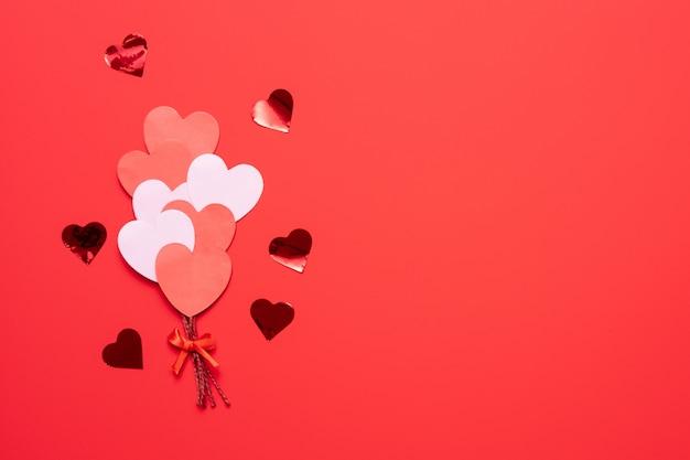 De dagachtergrond van valentine met rode en roze vlakke harten zoals ballons op roze vlakke achtergrond, legt