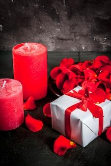 De dagachtergrond van valentine met roze bloembloemblaadjes, wit verpakte giftdoos met rood lint en vakantie rode kaars, op donkere steenachtergrond, exemplaarruimte