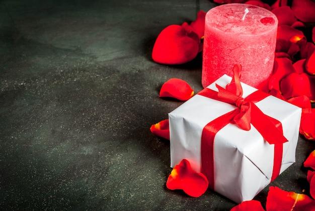 De dagconcept van valentine, met roze bloembloemblaadjes en wit verpakte giftdoos met rood lint, op donkere steenachtergrond, exemplaarruimte