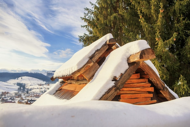 De daken van huizen in de sneeuw met lucht en wolken
