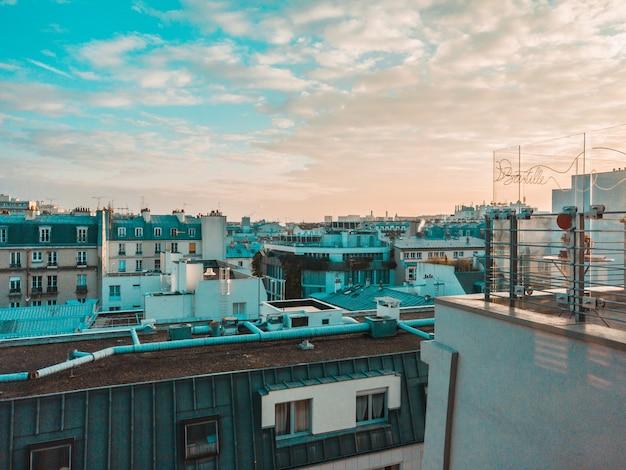 De daken van stadsgebouwen en bewolkte hemel