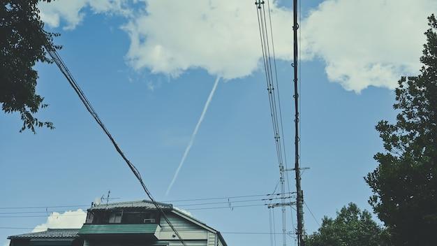 De daktop en veel overstekende kabels die op een zonnige dag de huizen op straat binnenlopen met blauwe lucht.