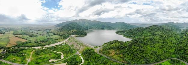 De dam van het luchtmeningspanorama met weg en rivier in de berg
