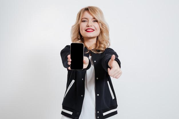 De dame die vertoning van mobiele telefoon toont en beduimelt omhoog