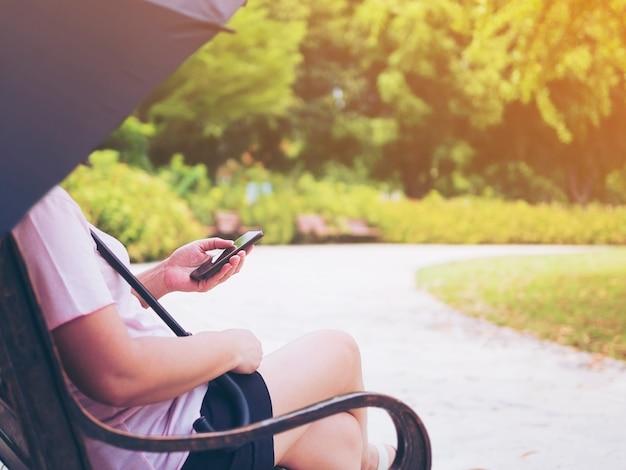 De dame ontspant zitting in het park met paraplu en gebruikt mobiele telefoon