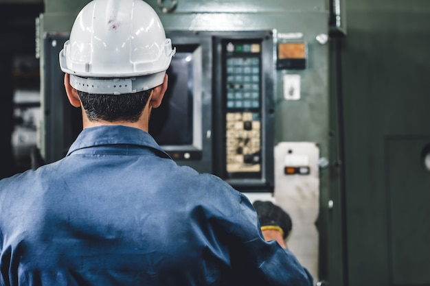 De de fabrieksarbeidersmens van de close-up stelt de machine in werking, de industrie van het de vaardigheidsarbeidwerk met veiligheidskleding.