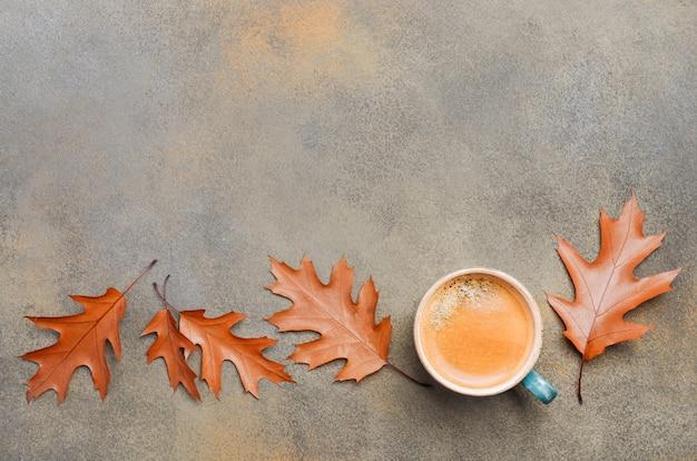 De de herfstsamenstelling met kop koffie en de herfstbladeren op steen of concrete achtergrondvlakte leggen de hoogste ruimte van het meningsexemplaar