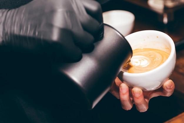 De de holdingsmelk van barista voor maakt koffie latte kunst in koffiewinkel
