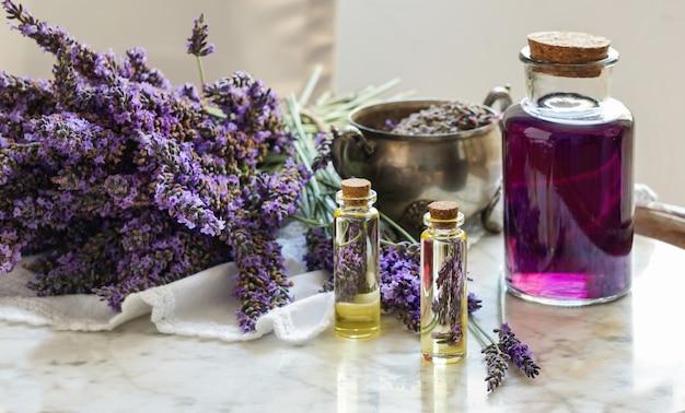 De de olieflessen van de lavendel, natuurlijk kruid kosmetisch concept met lavendel bloeien flatlay op steenachtergrond