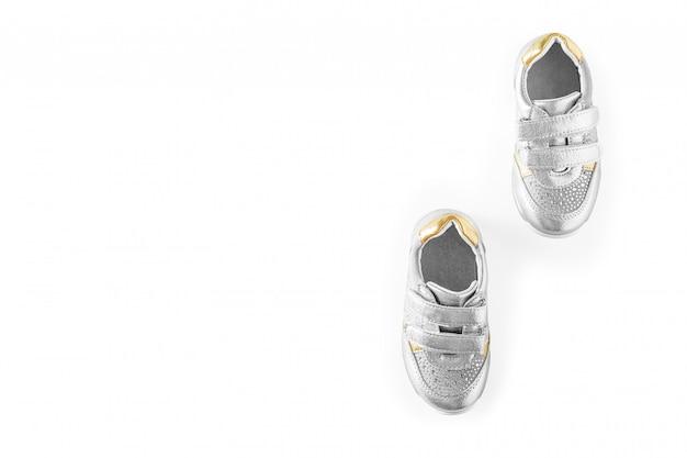 De de sportenschoenen van zilveren die kinderen op een witte achtergrond worden geïsoleerd