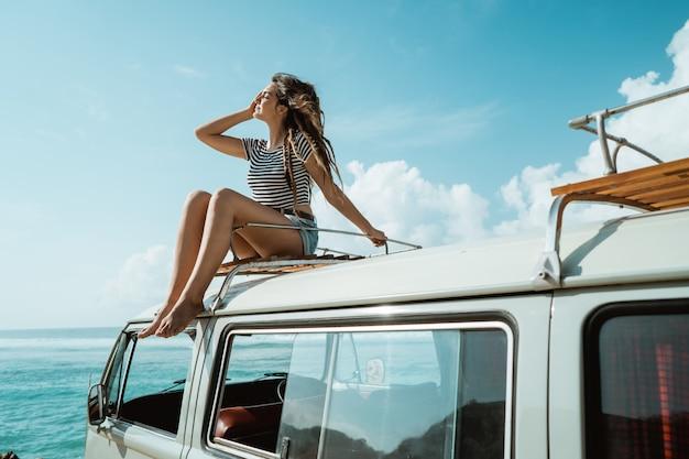 De de vrouwenzitting van de schoonheid geniet van slagwind op het dak