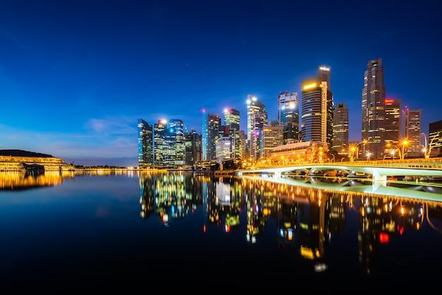 De de wolkenkrabberbouw van singapore in het district van de binnenstad met waterbezinning in marina bay in nacht, singapore.