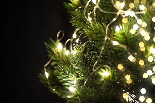 De decoratie van de kerstboom steekt zwarte achtergrond aan