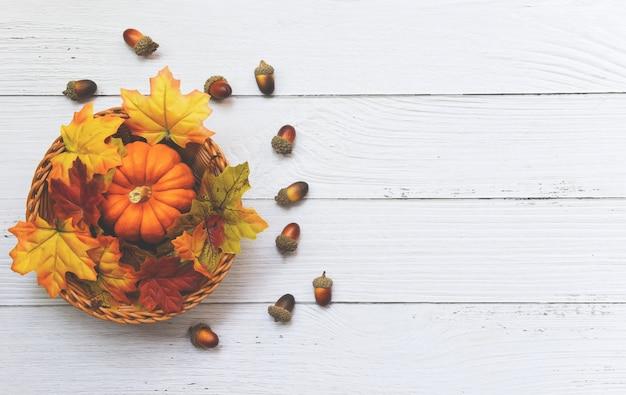 De decoratie van het de herfstblad van het dankzeggingskader feestelijk op houten, de herfstlijst die met pompoenen op mand op houten plaatsen