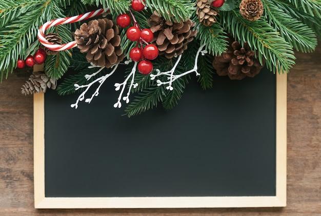 De decoratieachtergrond van kerstmis met bord of bord, pijnboombladeren en kegels en hulstballen op houten lijst
