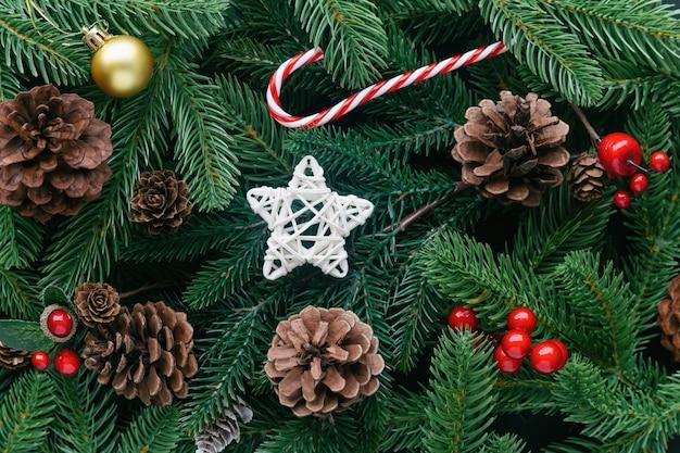 De decoratieachtergrond van kerstmis met pijnboombladeren, denneappels, hulstballen