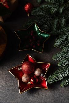 De decoratieballen en bessen van de kerstmissnuisterij op sterplaat, kerstboom op donkere achtergrond