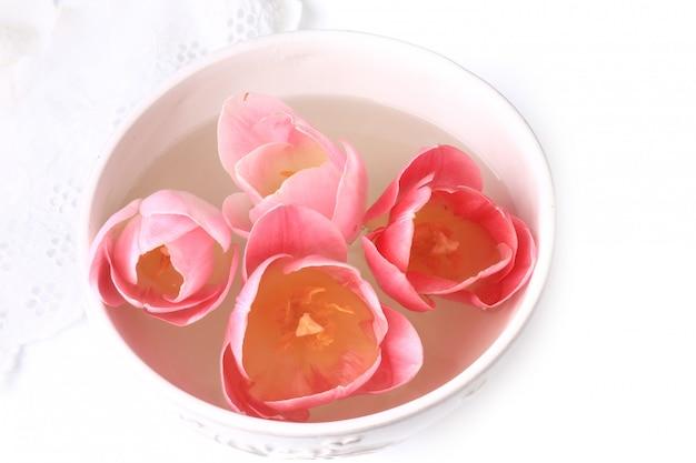 De decoratietulpen van de lente in een ceramisch kom wit kant als achtergrond