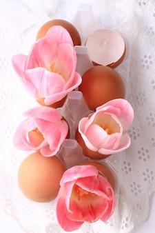 De decoratietulpen van de lentepasen in eierschalen op een wit delicaat kant als achtergrond