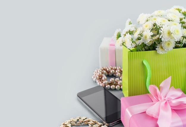 De decoratieve samenstellingsdozen met giften bloeit de juwelen van vrouwen het winkelen vakantie grijze achtergrond.