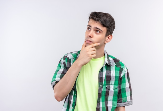 De denkende blanke jonge kerel die groen overhemd draagt, legde zijn hand op de kin op geïsoleerd wit