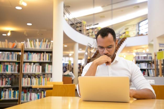 De denkende hand van de jonge mensenholding op kin en het bekijken laptop