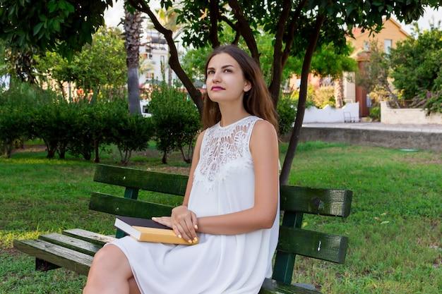 De denkende vrouwelijke student zit en houdt een boek in het park