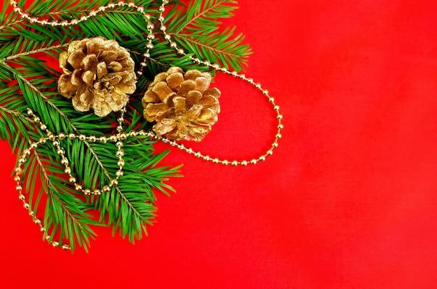 De dennentakken, twee gouden kegels, gouden ornamenten tegen rode zijde