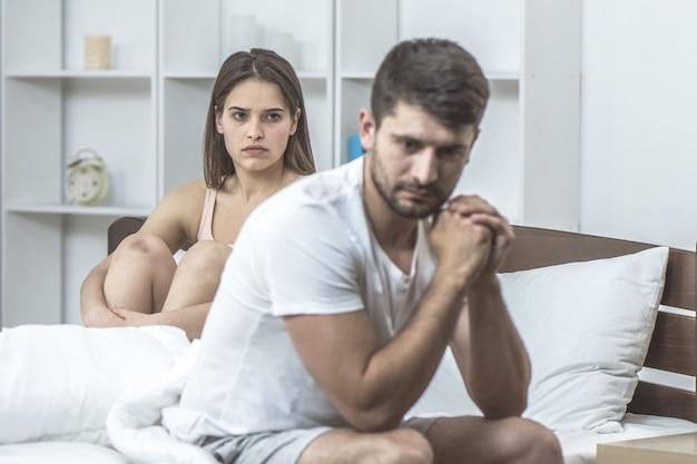 De depressieve man zit naast de vrouw in bed