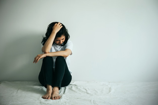 De depressieve vrouw omhelsde haar knie en huilde. triest vrouw zit alleen in een lege kamer.