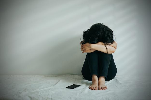 De depressieve vrouw omhelsde haar knie en huilde. trieste vrouw zat alleen met een telefoon naast haar.
