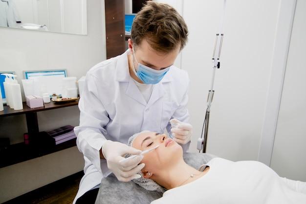 De dermatoloog brengt voedingscrème op de jonge en mooie vrouwenhuid om haar huid glad en gezond te maken.