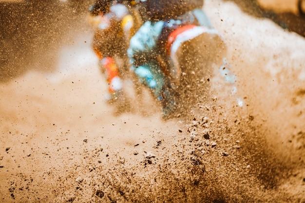 De details van vliegend puin tijdens een versnelling met bergfietsen rennen in vuilspoor in zonneschijndag