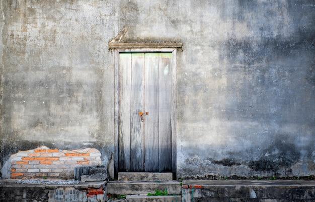 De deur en de donkere concrete muur oude retro kijken in thailand, beton geschikt voor de assemblage of het gebruik van een ruimte van het ideexemplaar