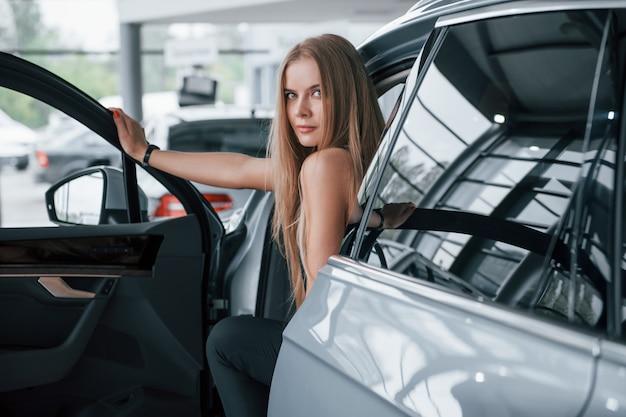 De deur openen. meisje en moderne auto in de salon. overdag binnenshuis. een nieuw voertuig kopen