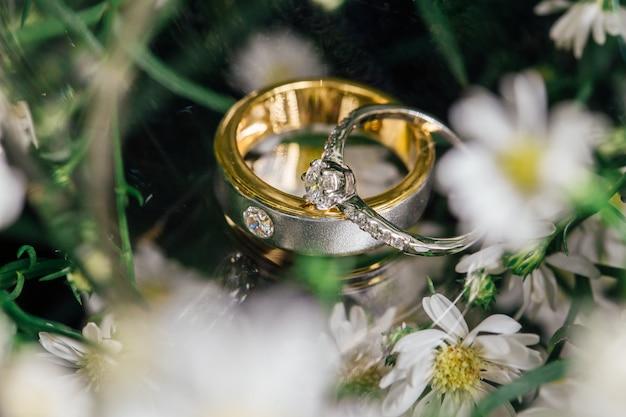 De diamanten paartrouwringen worden op glas geplaatst.