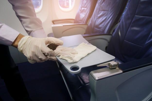 De dichte omhooggaande hand draagt handschoenen die vliegtuigstoel schoonmaken voor covid-19 preventie pandemie